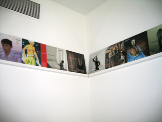 A photo of a corner shelf in a white room, that has color photos lined up along it.